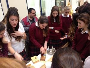 Durante la visita, algunas alumnas han probado a bruñir una tabla dorada al agua.